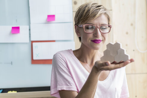 Woman holding wooden building blocks in modern office - RIBF00655