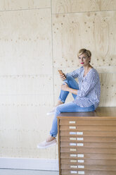 Businesswoman sitting on filing cabinet in creative office - RIBF00667
