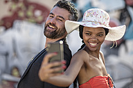 Smiling man and woman taking a selfie with cell phone - ZEF11657