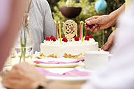 Hand lighting candles on 80th birtday cake - MFRF00767