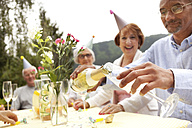 Senior people celebrating, man pouring champagne into glass - MFRF00779