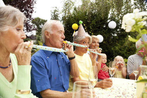 Extended family and friends having birthday party in garden - MFRF00791