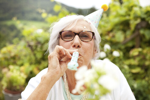 Senior woman blowing party blower - MFRF00794