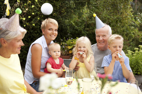 Extended family and friends having birthday party in garden - MFRF00803