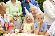 Extended family and friends having birthday party in garden - MFRF00806