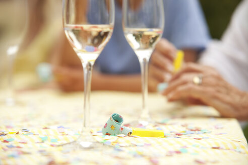 Party blowout and glasses of champagne on table - MFRF00812