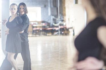 Couple dancing tango in front of mirror in studio - ZEF11737