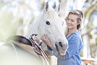 Smiling woman with horse on horse farm - ZEF11744
