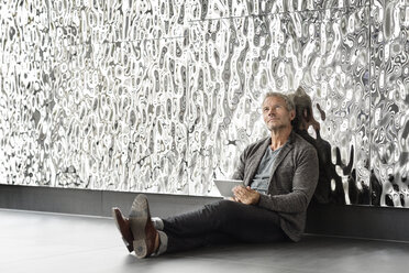 Businessman sitting at rippled wall with tablet looking up - PESF00368