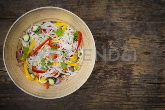 Bowl of glass noodle salad with vegetables on dark wood - LVF05608