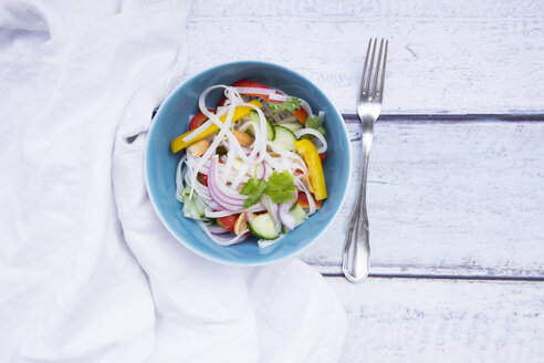 Bowl of glass noodle salad with vegetables, cloth and fork on wood - LVF05611