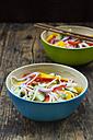 Bowls of glass noodle salad with vegetables on dark wood - LVF05620