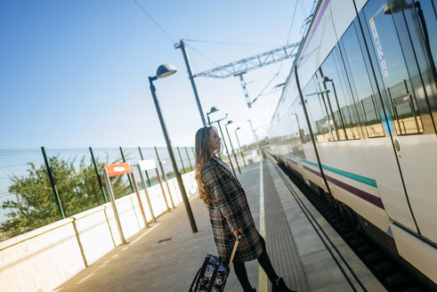 Woman walking towards a train car at a station - KIJF00864