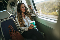 Woman on a train listening to music with headphones and drinking coffee - KIJF00873