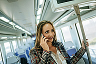 Smiling woman on a train talking on cell phone - KIJF00882