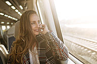 Smiling woman on a train looking out of window - KIJF00888