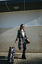 Smiling woman waiting with suitcase - KIJF00900