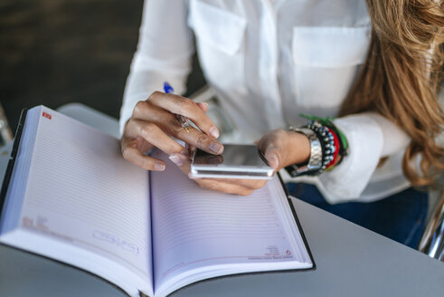 Close-up of woman's hands using a smartphone and a notebook - KIJF00906