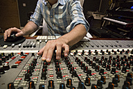 Hand of a man working in the control room of a recording studio - ABZF01530