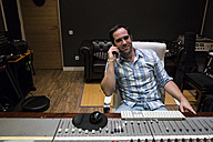 Smiling man in the control room of a recording studio on cell phone - ABZF01539