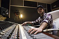 Man working in the control room of a recording studio - ABZF01545