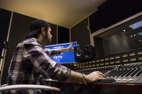 Man working in the control room of a recording studio giving ok sign - ABZF01551