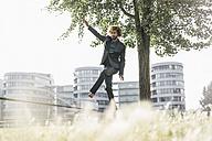 Young businessman balancing on slackline - JOSF00395