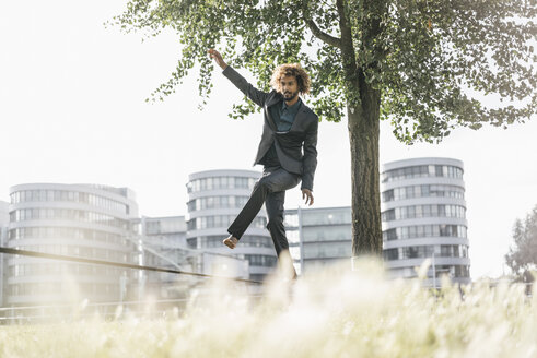 Young businessman balancing on slackline - JOSF00395