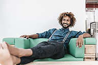 Young man relaxed in arm chair with feet up - JOSF00401