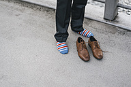 Young man in socks standing on street with leather shoes in front of him - JOSF00419