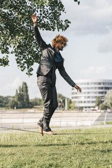 Young businessman balancing on slackline - JOSF00425