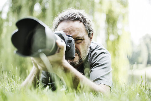 Man lying on a meadow taking pictures with camera - JATF00932