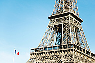 France, Paris, French Flag and part of Eiffel Tower in front of sky - GEMF01266