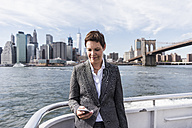 USA, Brooklyn, portrait of  businesswoman standing on boat looking at cell phone - UUF09249
