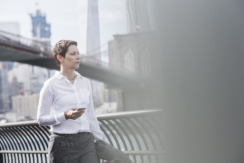 USA, Brooklyn, portrait of businesswoman with cell phone - UUF09258