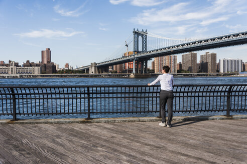 USA, Brooklyn, back view of  businesswoman looking at East River - UUF09267