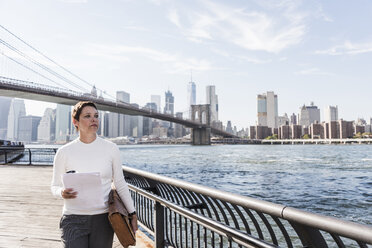 USA, Brooklyn, portrait of  businesswoman with documents standing in front of Manhattan skyline - UUF09270