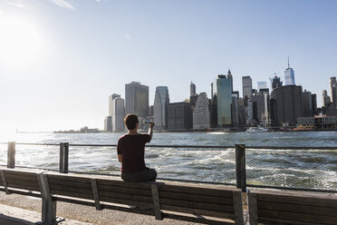 USA, Brooklyn, back view of woman  taking picture of Manhattan skyline with cell phone - UUF09273