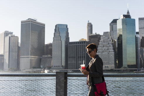 USA, Brooklyn, businesswoman looking at her smartphone in front of Manhattan skyline - UUF09276