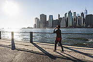 USA, Brooklyn, businesswoman drinking coffee to go in front of Manhattan skyline - UUF09279