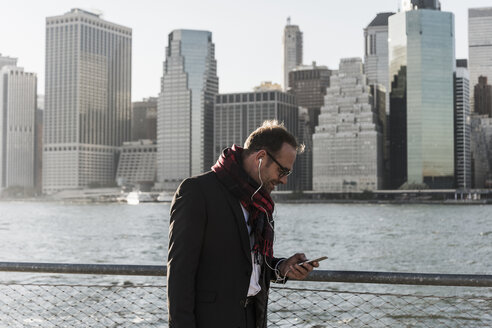 USA, Brooklyn, businessman with smartphone and earphones in front of Manhattan skyline - UUF09285