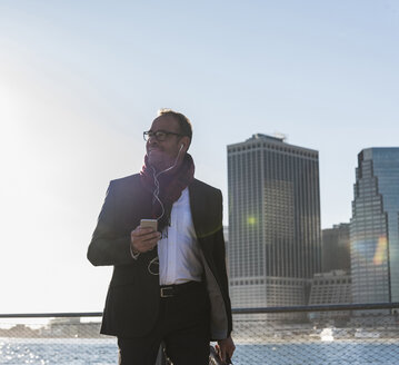 USA, Brooklyn, smiling businessman with earphones and smartphone in front of Manhattan skyline - UUF09288
