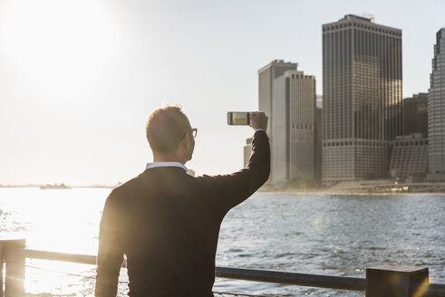 USA, Brooklyn, man taking picture of Manhattan skyscrapers with smartphone at evening twilight - UUF09294