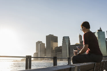 USA, Brooklyn, woman with coffee to go sitting on bench looking at smartphone - UUF09297