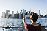 USA, Brooklyn, back view of woman taking picture of Manhattan skyline with tablet - UUF09300