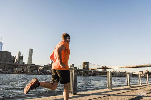 USA, Brooklyn, man jogging with headphones - UUF09306
