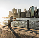 USA, Brooklyn, man doing stretching exercises in front of Manhattan skyline in the evening - UUF09309