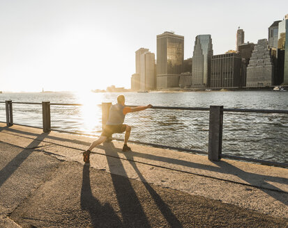 USA, Brooklyn, man doing stretching exercises in front of Manhattan skyline in the evening - UUF09312
