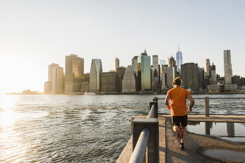 USA, Brooklyn, back view of man jogging in front of Manhattan skyline in the evening - UUF09315