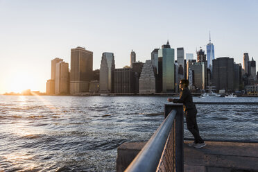 USA, Brooklyn, woman leaning on railing looking at view in the evening - UUF09321